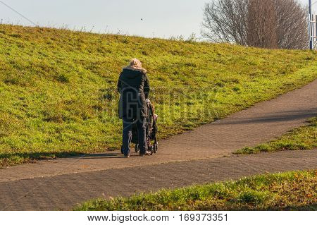 Young grandma with a baby carriage while walking with the grandson.