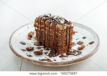 Beautiful dessert on a table. Delicious chocolate Spartak cake served on a beautiful rustic plate. International haute cuisine dessert.