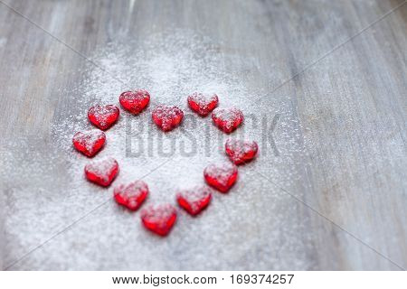 Marmalade in the form of hearts laid out in the shape of a large heart on wooden boards. poster