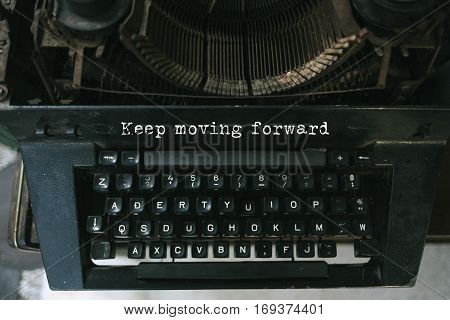 Typewriter with white paper page on wooden table. sample text Keep moving forward.