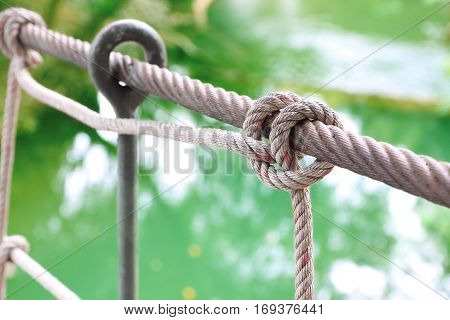 Rope knot of handrail suspension bridge cross river.