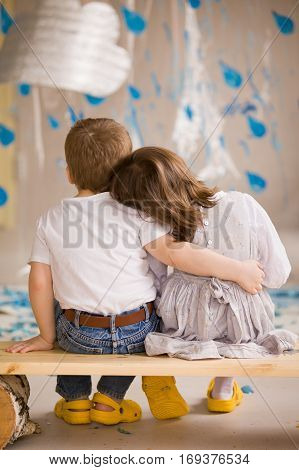 A little boy in blue jeans and white t-shirt and a small girl in a dress sitting on a wooden bench and watching clouds and rain. A boy is hugging a girl. Indoors decorations for a funny kids party.