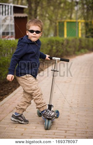 Cute small boy in sun glasses and scooter in a park. Riding a scooter. Kids activities outdoor.