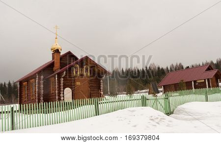 Verkhniy Tagil, Russia - 11.07.2016: Small wooden Church stands in the snow near the forest.