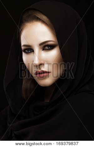 Beautiful girl in the Arab scarf with oriental make-up. Beauty face. Photos shot in the studio.
