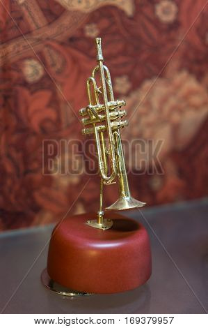 Gift trumpet music box on wood pedestal.