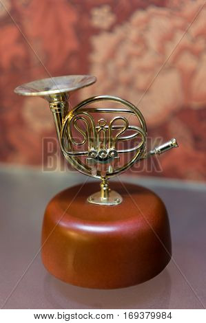 Gift horn music box on wood pedestal.