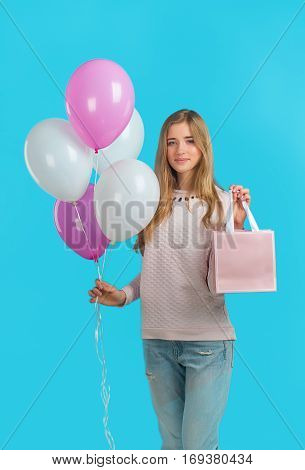 Sweet Nice Girl With Baloons And Little Prersents Bag In The Hands On The Blue Background. Shopping