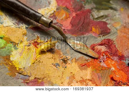 spatula on a palette with oil paints. yellow paint extruded from the tube