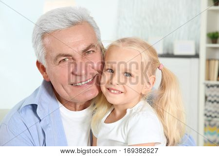 Cute little girl with grandfather in living room