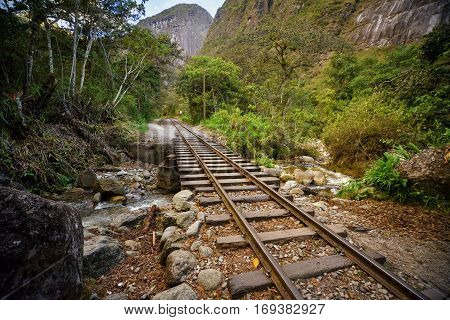 Railway track crossing jungle and Urubamba river, connecting Machu Picchu village to hydroelectric station, mostly used for tourism and cargo purpose.