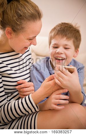 Portrait of smiling woman with cute kid boy looking into a smartphone and laughing. Mother with child with telephone. Happy family. Technology and communication concept