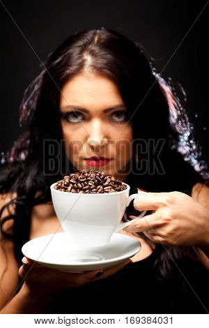 young woman holding a cup of coffee beans