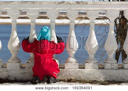 Little child in a red jumpsuit and blue hat sitting and looking at the river though white fence. Spring sunny day at the beach. Walking outdoors and enjoying river view. Watching at the water.