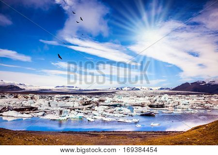 The concept of extreme tourism. Ice floes are reflected in the water surface lake. Cool northern sun illuminates the Ice Lagoon, Iceland