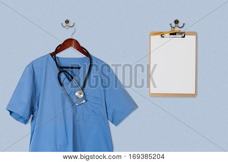 Blue medical scrubs uniform shirt hanging on a hanger with stethoscope and on hanger and hook on blue wall with clipboard for message