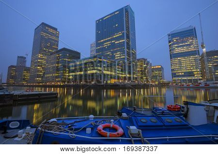 The reflection of the office buildings in Canary Wharf at London United Kingdom early in the morning .