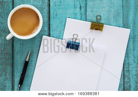 Blue Wooden Desk Table With Paper Reams, Pen And Cup Of Coffee.