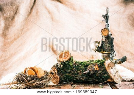 Metal coffee cups on undressed logs and cookies in bird nest. Eco style