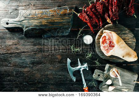 Pork leg and chopper for meat. Various spices on wood boards