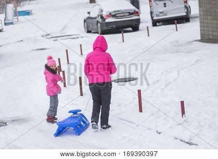 DNEPR UKRAINE - DECEMBER 03 2016:Mother with daughter getting ready to sledge on a snowy street in Dnepr, Ukraine at December 03, 2016