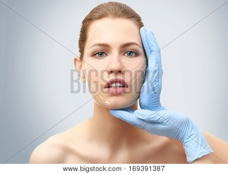 Plastic surgery concept. Doctor examining female face, light background
