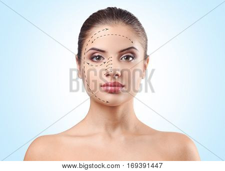 Young woman with marks on face against blue background. Plastic surgery concept