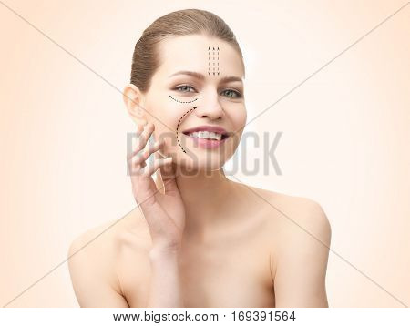 Plastic surgery concept. Young woman with marks on face against color background