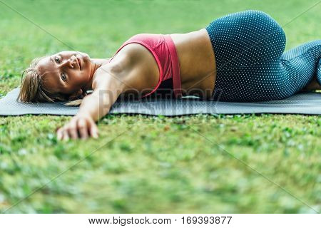 Young woman doing Yoga reclining spinal twist position