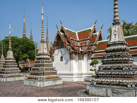 Thailand Bangkok. Temple of the Reclining Buddha (Wat Pho). Small mortars (there are ninety-one thing in the temple) on the background of temple buildings.