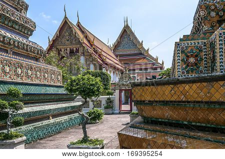 Thailand Bangkok. Temple of the Reclining Buddha (Wat Pho). The biggest chedi in height forty-one meter- a green decorated with images of the Buddha; yellow erected in honor of King Rama the third.