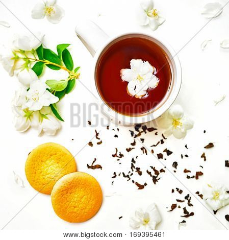 Tea Cup With Dried And Fresh Jasmine Flowers And Cookies