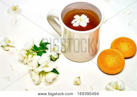 Tea Cup With Fragrant Jasmine Flowers And Biscuits On Background