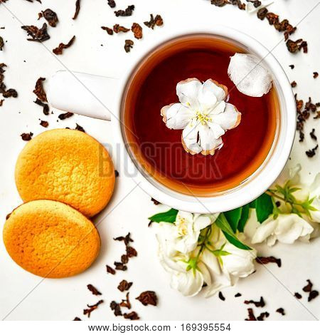 Teacup With Dried And Fresh Jasmine Flowers And Cookie