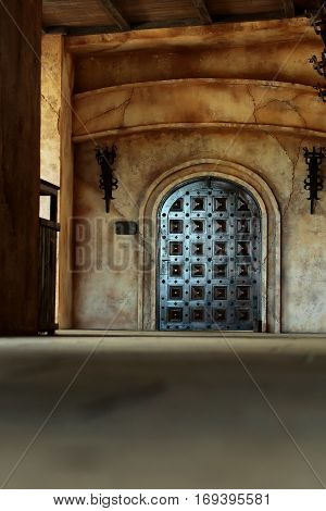 Old wooden arch door medieval style portal in dark brown color on stone building and blurred floor on cracked cement wall background