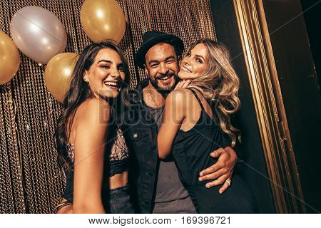 Portrait of handsome man with female friends at disco. Young friends in a party at nightclub.