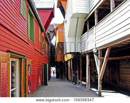 Bergen, Norway - June 8, 2009: Walk between the historic wooden houses of the old town location Bryggen in Bergen (Norway).