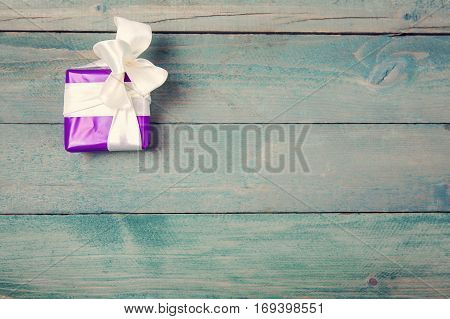 Violet gift box with bow on wooden background