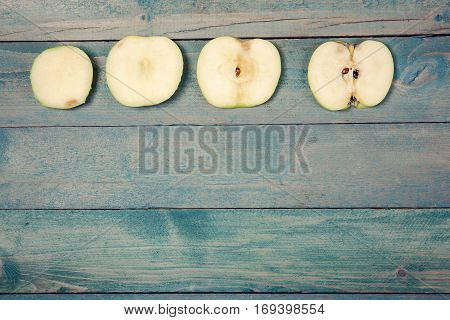 Four ripe apple slices on old wooden background. Top view