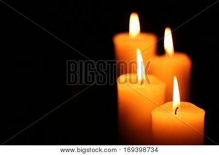 Four big different burning candles. Bright light on dark background. RIP darkness template. Birthday party. Romantic evening on Valentine.