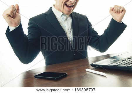 business man working at office with laptop on his desk. He rejoices in the success