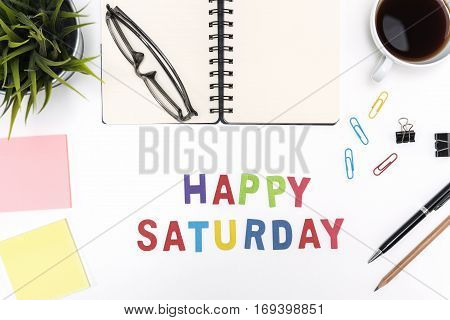 Office desk table with supply pen pencil notebook computer eye glasses sticky note cup of coffee and happy saturday word on white background