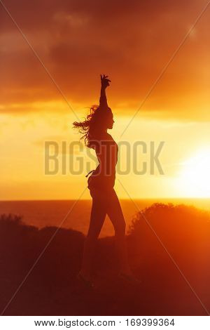 Black Silhouette Of Pretty Girl On Sea Beach At Sunset