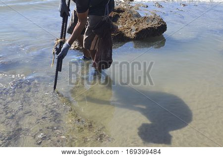 A native of Mexico is spearing for oysters long the edge of rocks.