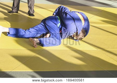 Two young judoka in a kimono struggling on the tatami in the gym