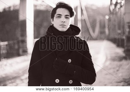 Retro portrait of a handsome hipster guy standing on the bridge looking at camera. Black and white retro photo with grain