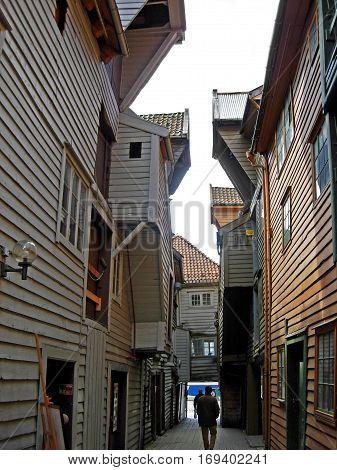 Bergen, Norway - June 8, 2009: People walk between the historic houses of the old town location Bryggen in Bergen (Norway).