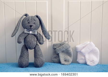 gray toy rabbit standing next to a white and gray socks