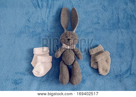 gray toy rabbit lies next to a white and gray socks