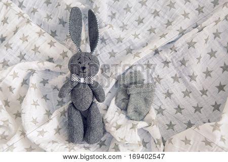 gray toy rabbit lies next to a gray socks